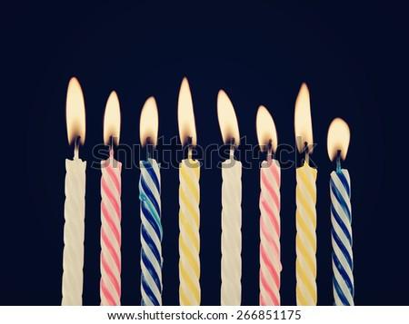 Burning birthday candles on blue background - stock photo