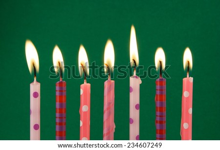 Burning birthday candles on green background