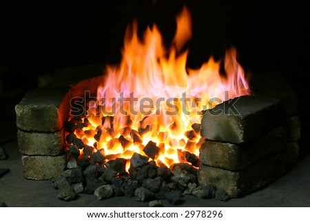 Burning black coal in the forge imposed by a brick