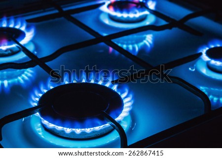 Burning blue gas. Focus on the front edge of the gas burners - stock photo