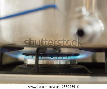 Burning blue gas on the kitchen stove - stock photo