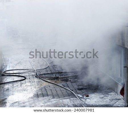 Burning building with smoke and fire fighters in background - stock photo