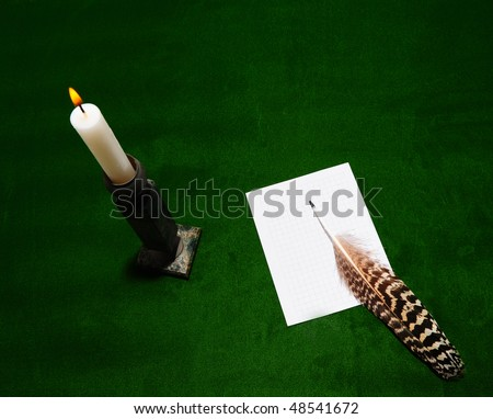 Burning Candle, a Sheet of Squared Paper and a Feather on the Green Table - stock photo
