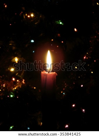 burning candle and lights on the christmas tree background,  shallow depth of field - stock photo