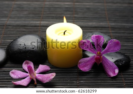 burning candle and massage stones and with orchid on bamboo stick straw mat - stock photo