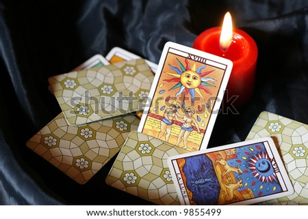 Burning candle and tarot cards-sun and moon - stock photo