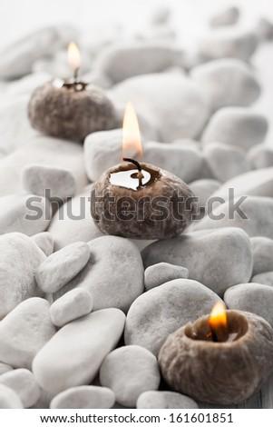 Burning candle and white stones - stock photo