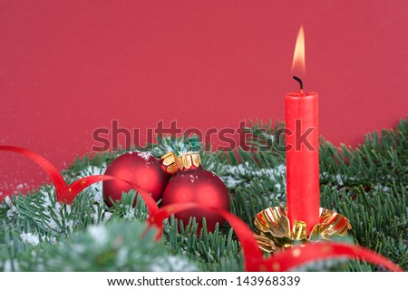 Burning candle and Xmas balls on fir twigs with snow on red background, copy space - stock photo