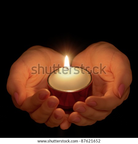 Burning candle in female hands. A black background - stock photo