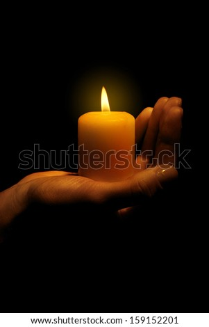 Burning candle in hand isolated on black - stock photo