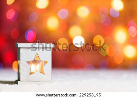 Burning candle, in snow, with defocussed fairy lights, boke in the background, Festive Christmas background with copyspace - stock photo
