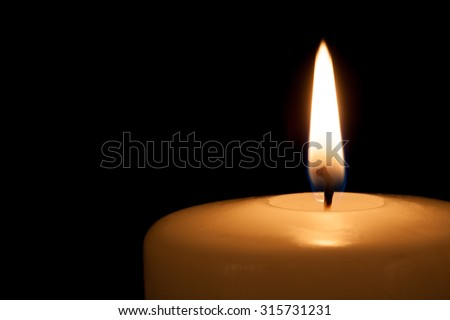 Burning candle in the dark with free copy space - stock photo
