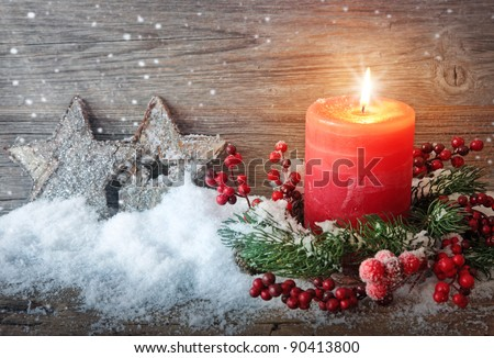 Burning candle in the snow - stock photo