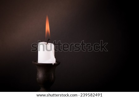 burning candle on a dark background.