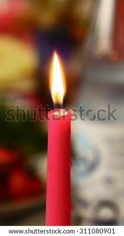 Burning candle on a table . - stock photo