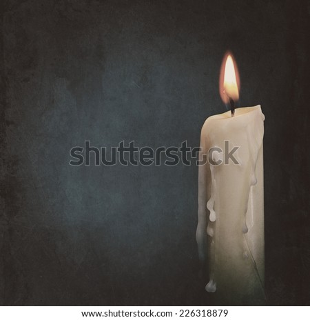 Burning candle over dark backgrounds. Abstract grungy still life