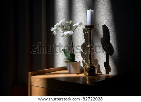 Burning candle, white orchid flowers and shadows on the wall - fragment of church interior - stock photo