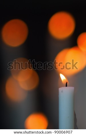 burning candle with bokeh blur in the background - stock photo