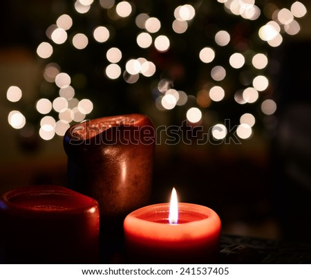 Burning Candle with Holiday Lights in Background