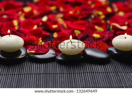 burning candle with zen stones and red petals on wooden mat - stock photo