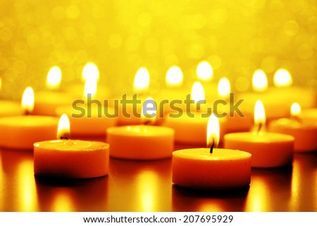 burning candles against yellow bokeh background - stock photo