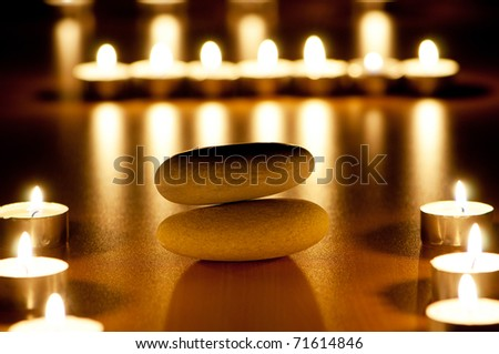 Burning candles and pebbles for aromatherapy session - stock photo