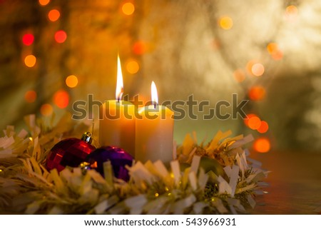 Burning candles in a Christmas decoration on the background lights and bokeh