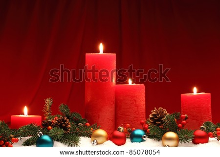 Burning candles in a Christmas setting with seasonal decorations. - stock photo