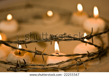 Burning candles in barbed wire, symbol of hope and civil rights - stock photo