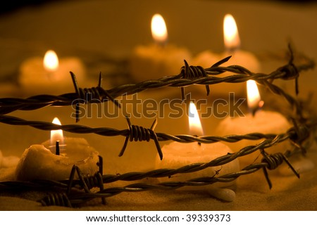 Burning candles in barbed wire, symbol of hope and freedom - stock photo