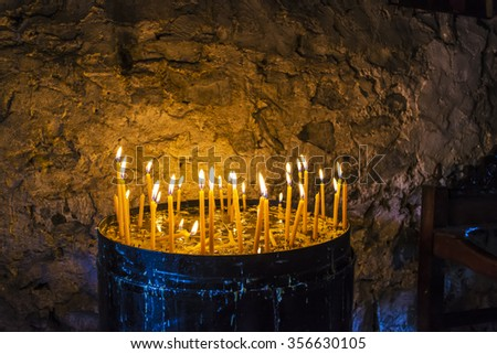 Burning Candles inside a Stoned Monastery - stock photo