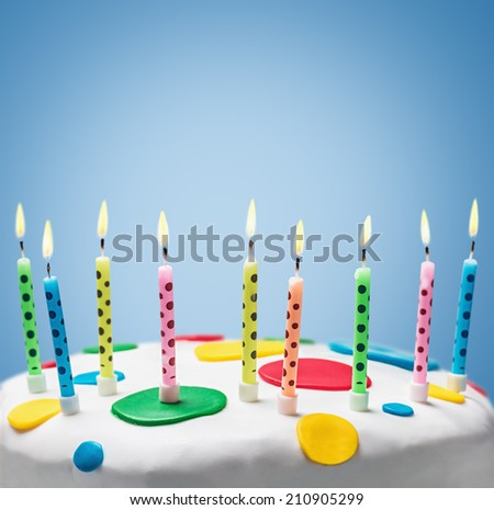 burning candles on a birthday cake on blue background