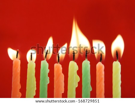 Burning candles on red background