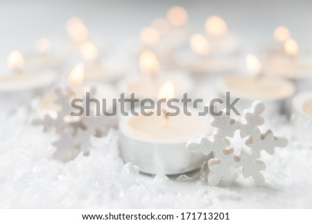 burning candles with artificial snow - stock photo