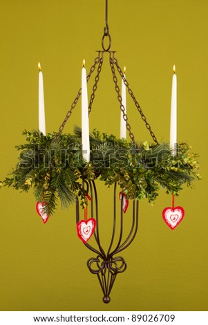 Burning candlestick with Christmas decoration and a green background - stock photo