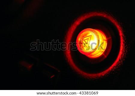 Burning car emergency button at night on plastic panel - as danger symbol. Closeup shot. - stock photo