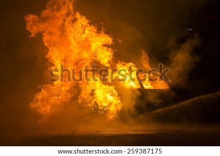 Burning car on the road - stock photo