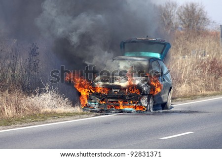 burning car on the road - stock photo