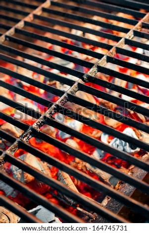 Burning charcoal in barbecue and glowing empty grill - stock photo
