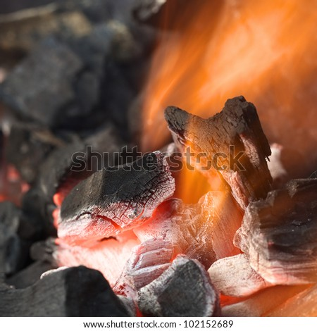 Burning charcoal with orange-colored flame and glow (Selective Focus, Focus on parts of the charcoal pieces around the flame) - stock photo