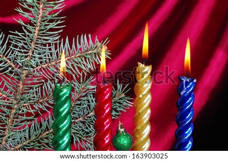 Burning Christmas candles with decoration against purple drapery - stock photo