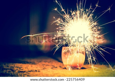 burning christmas sparkler isolated on black background - stock photo