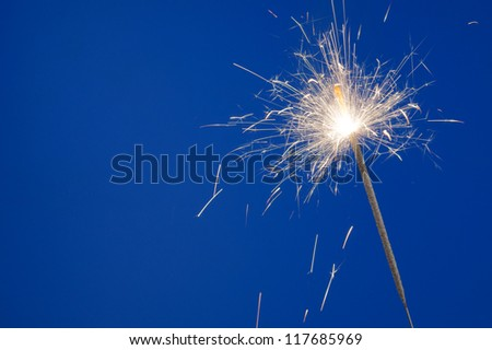 Burning christmas sparkler on blue background with room for text - stock photo