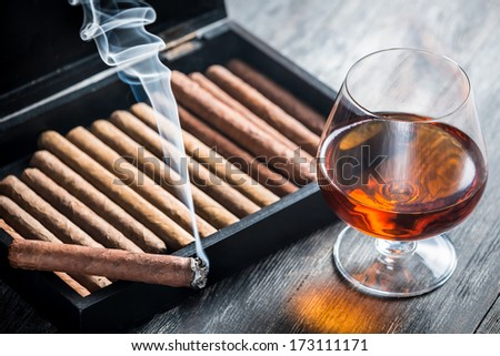 Burning cigar and cognac in glass - stock photo