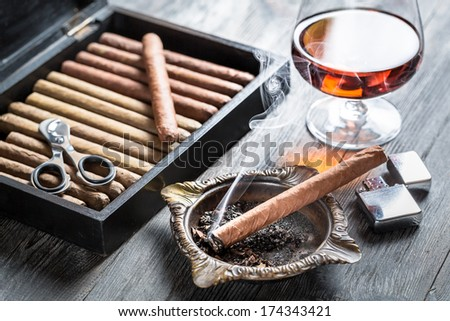 Burning cigar in ashtray and cognac - stock photo