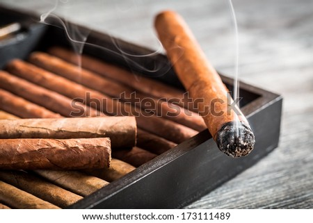 Burning cigar with smoke on old humidor - stock photo