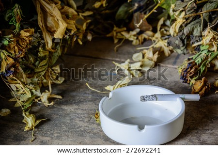 Burning cigarette in ashtray on grunge wood table - stock photo