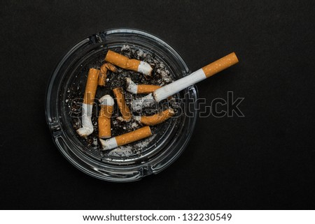 Burning cigarette left in ashtray on black background - stock photo