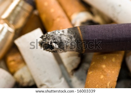 burning cigarette on cigarette butt background - stock photo