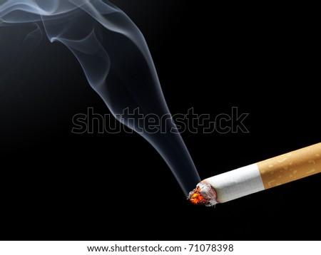 Burning cigarette with smoke on black background - stock photo
